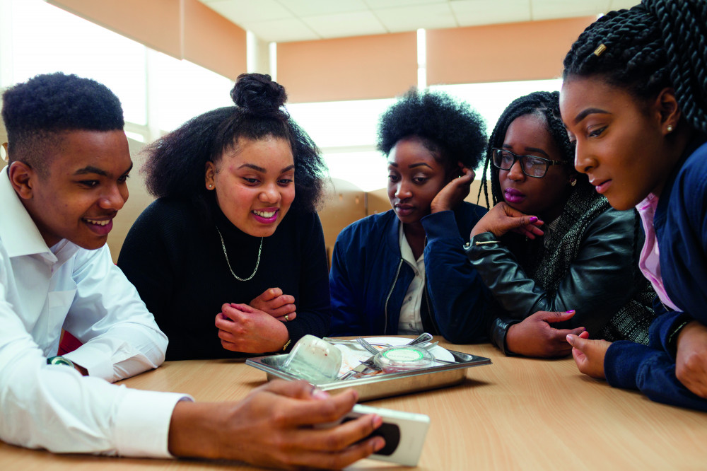 A group of five young people sat at a table in a school looking at a mobile phone
