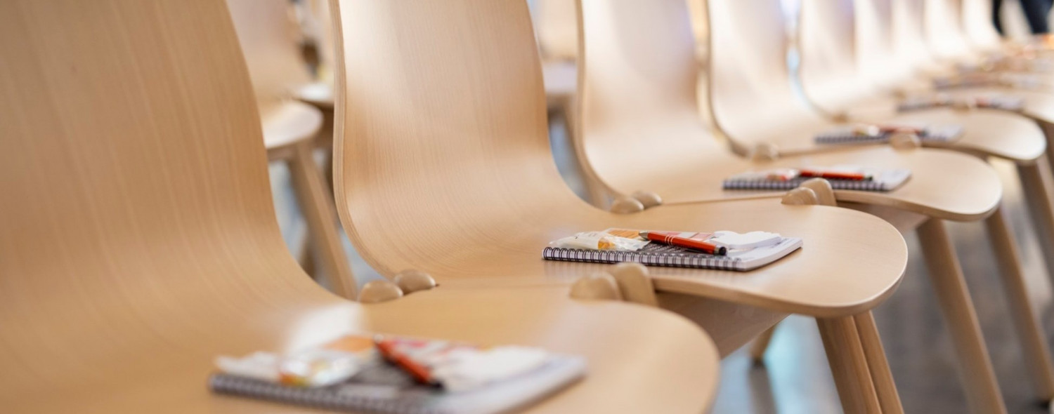 Row of chairs with notepads and pens