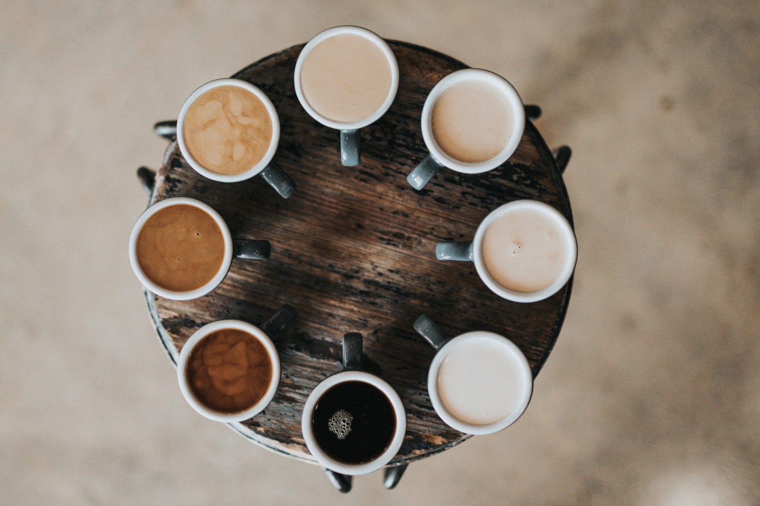 Cups of different coloured coffee on a circular table
