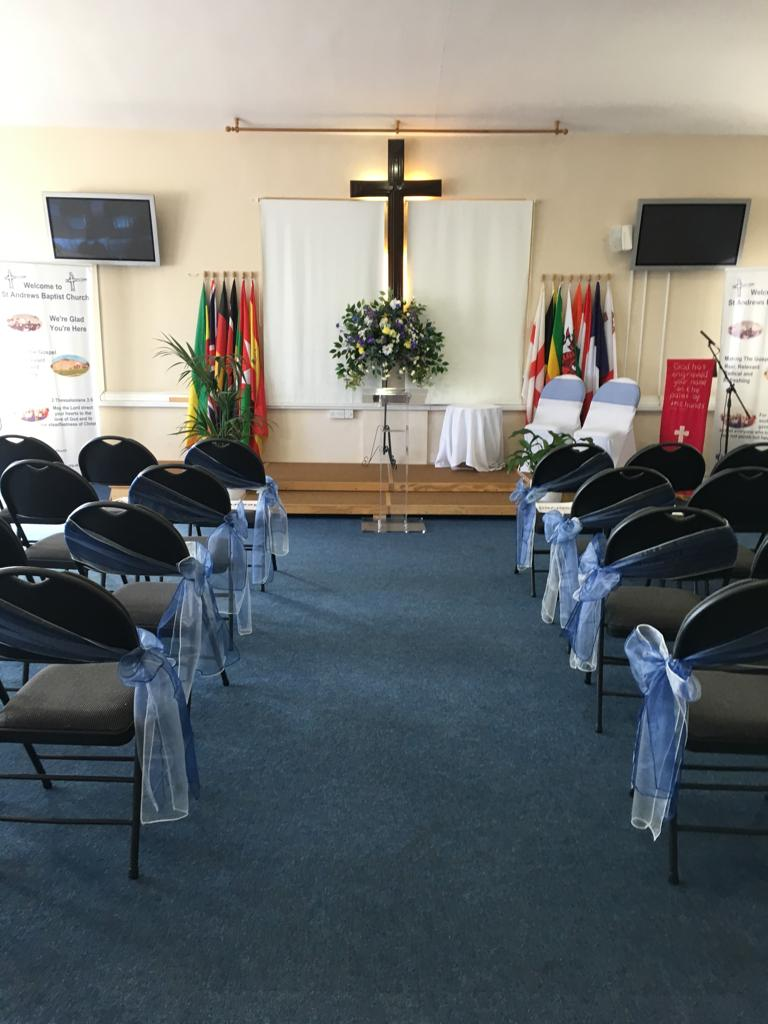 photo of the church set up for a wedding with grey chairs and blue ribbons