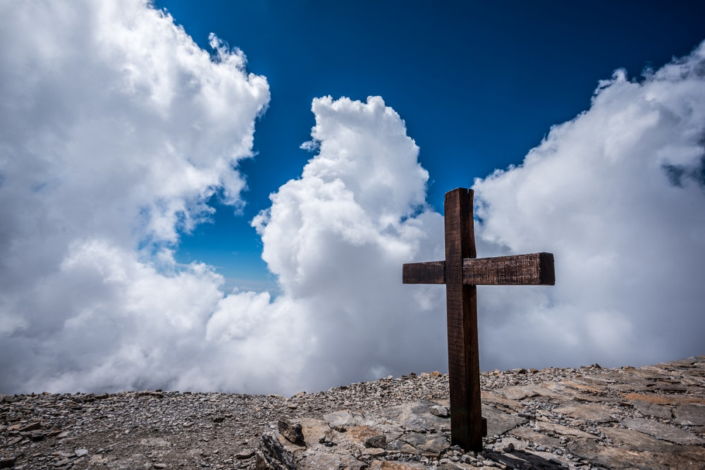A photo of a cross against a blue sky with clouds