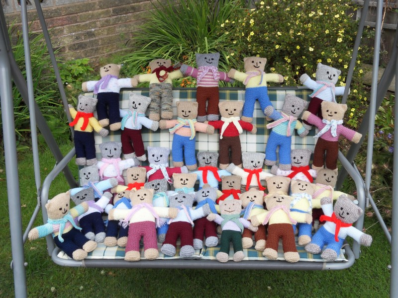 Knitted teddy bears on a swing in the garden