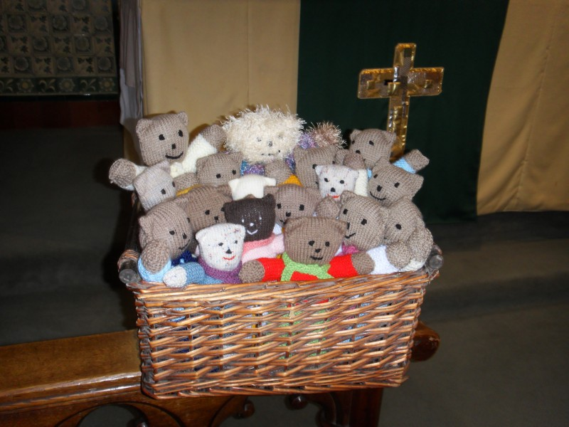 Knitted teddy bears in a basket in front of an altar cross