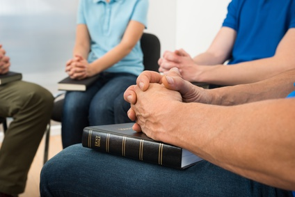 Group of people sitting with hands clasped  in prayer with bibles on their laps.