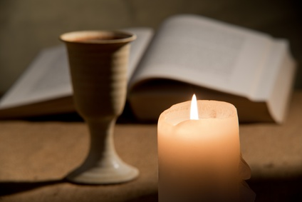 Photo of pottery chalis, candle and open Bible