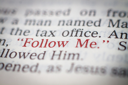 Photo of a page from the Bible with the words 'Follow me' picked out in red print.