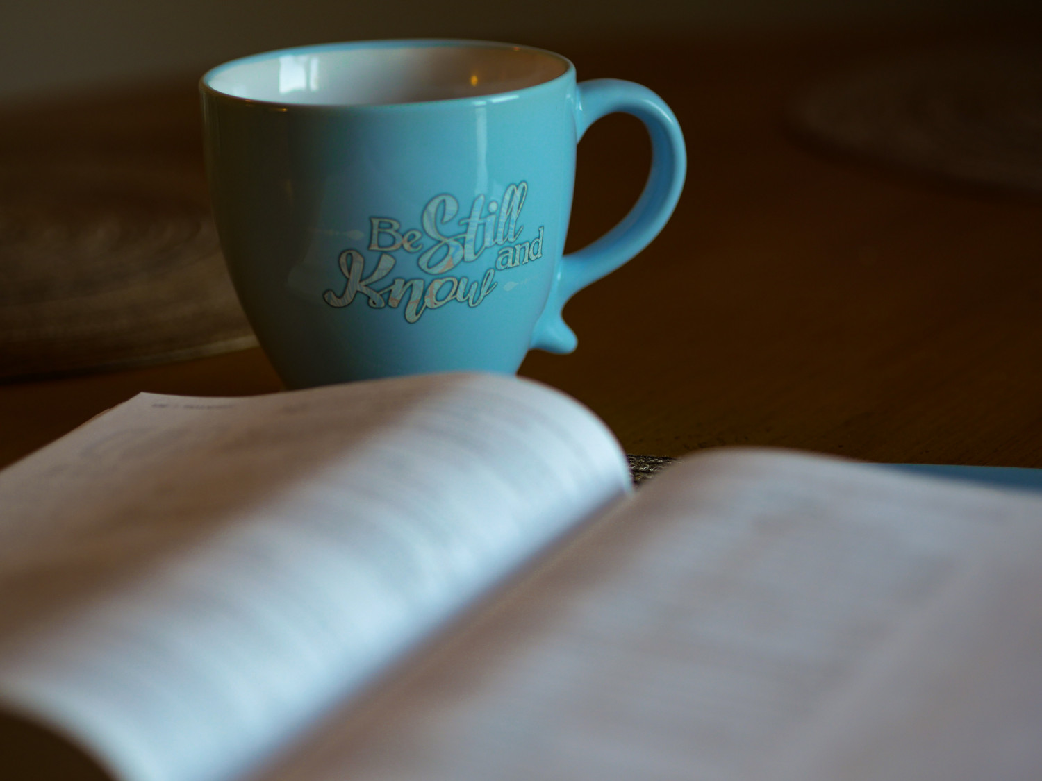 Bible and a mug with the words Be Still