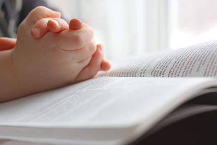 Photo of young child's hands on the Bible