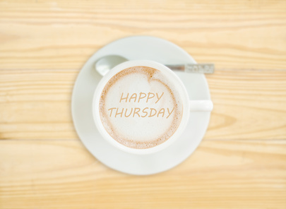 Photo of a cup of Cappucino coffee with the words 'Happy Thursday' written in the coffee
