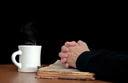 Photo of woman's hands clasped in prayer upon an open bible