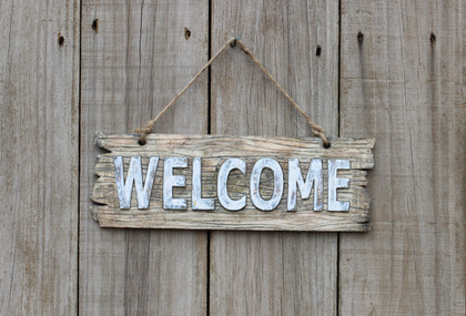 Photo of a Welcome Sign hanging on a Shed door.