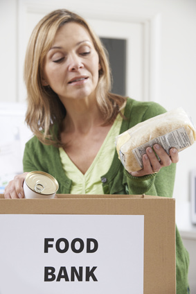 Photo of woman putting a bag of pasta into a box marked 'Food Bank'.