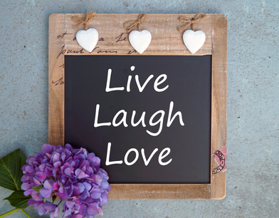 Photo of blackboard with hanging hearts & the words Live, laugh, love.