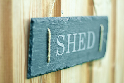 A slate sign on a door with the word SHED written on it.