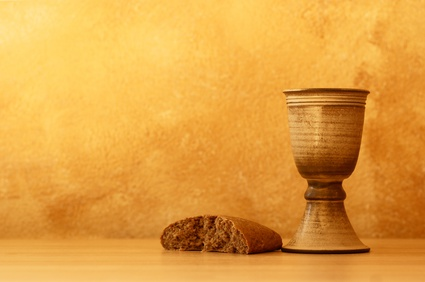 Photo of torn loaf of bread and pottery Communion chalis.