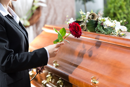 Photo of a person placing a rose on a coffin