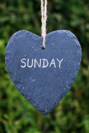 Photo of a slate hanging heart with the word 'Sunday' written on it.