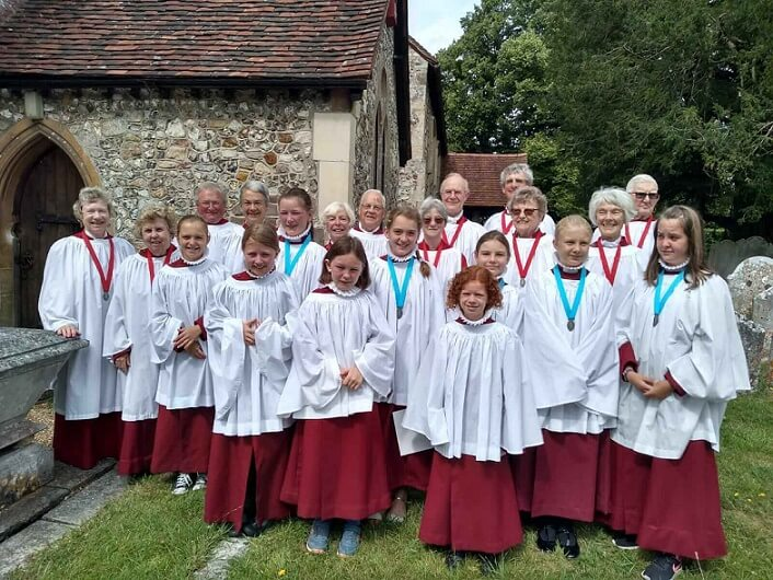 Choristers standing outside the church in their robes and surplices