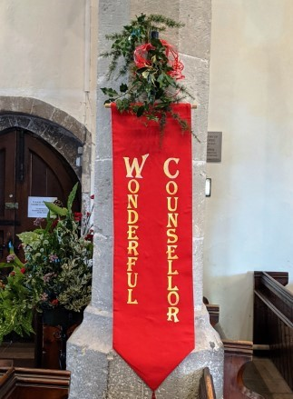 Red banner at entrance of the church with words 'Wonderful Counsellor'