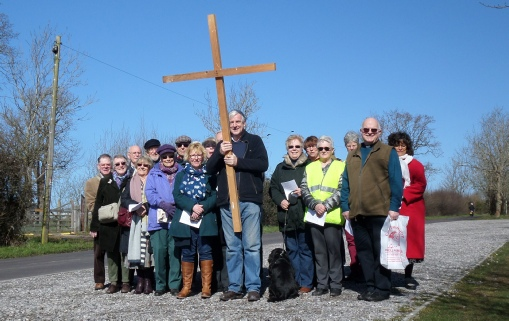 Gathering of people stood with a large wooden cross to symbolise Good Friday