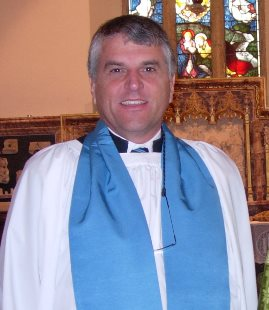 Reader of the parish dressed in white surplice with blue scarf