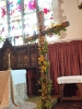 Flowers adorn the cross, bringing 'new life', in contrast to the barren cross of Good Friday