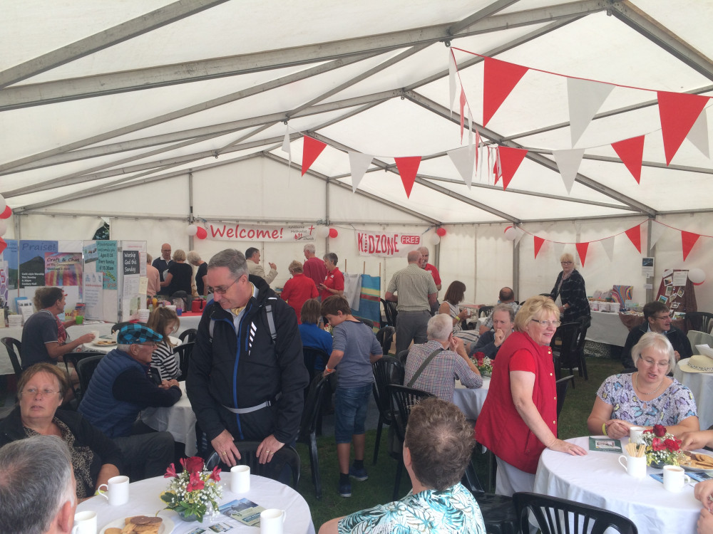 Photo showing the inside of a marquee full of people sat at tables enjoying refreshments