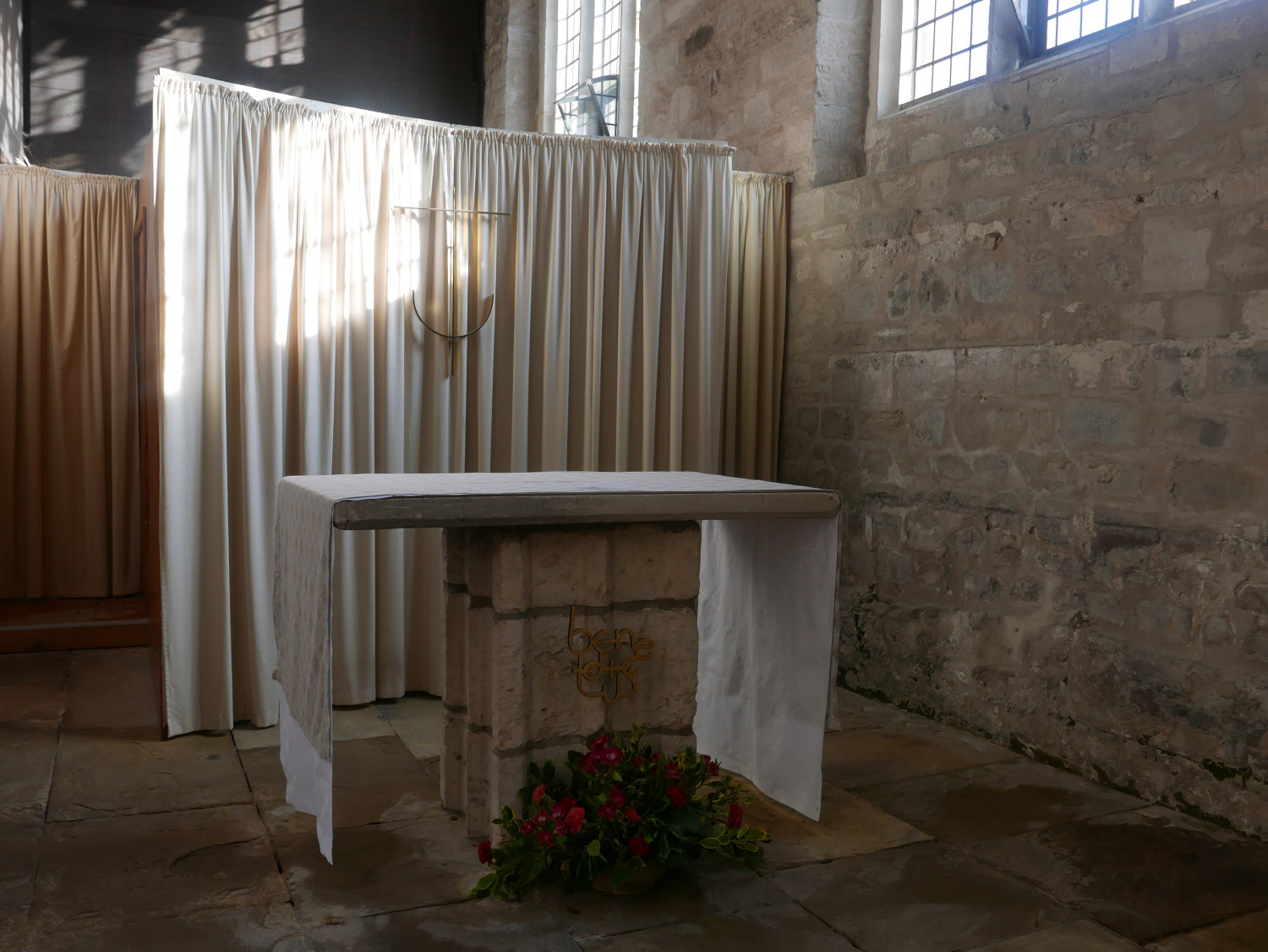 Photograph of an altar inside the Benedict Chapel at King's Lynn Minster. There is a white cloth on the stone altar and flowers in front. Behind is a white drape with a golden crucifix attached.