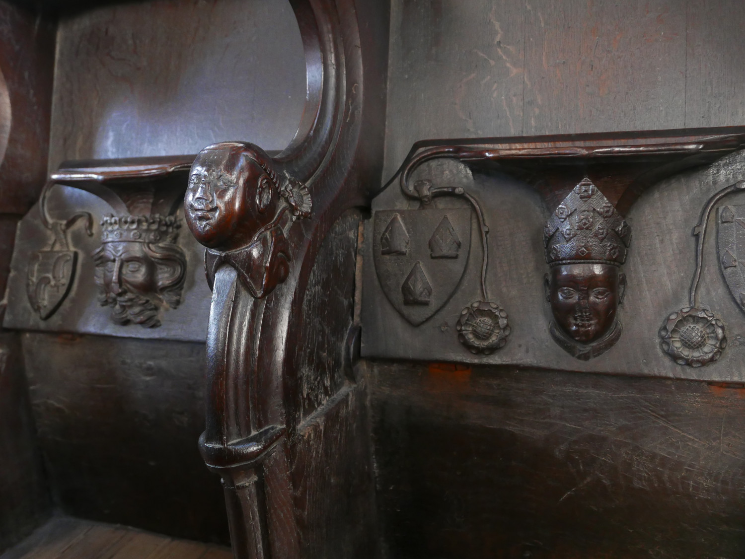 Photograph of the misericord seats in the chancel of King's Lynn Minster. The seats are folded to reveal intricate carvings of the heads of Edward the Black Prince and Bishop Henry Despencer.