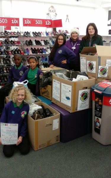 Buntingsdale primary students, head hilary alcock at Clarkes Shoe shop in Stoke Mothercare handing over boxes and boxes of shoes