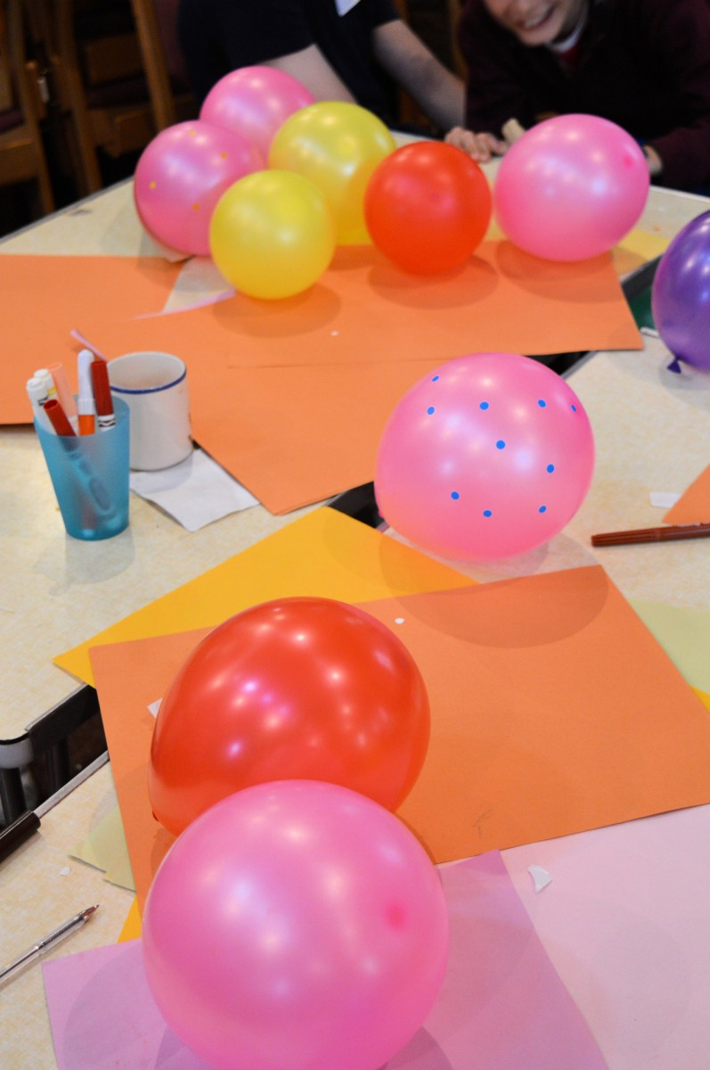 Picture of balloons, coloured paper and pens on a table