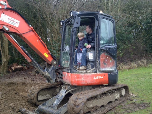 Trevor Tack in his digger, with little helper at Spiritual Garden