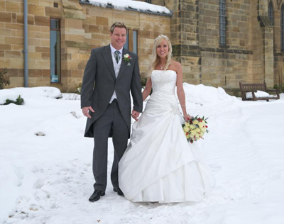 A bride and groom in the snow at St Mary's