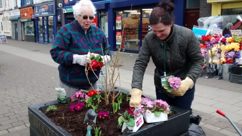image of volunteers planting flowers