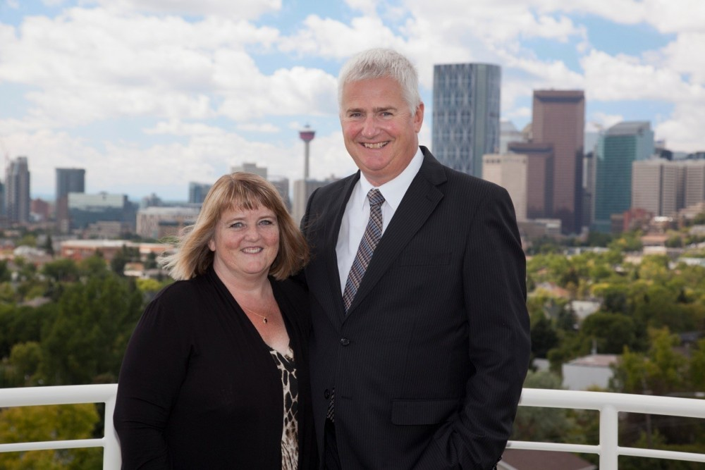 Tim & Christine Hayes standing on the roof of one of their congragation's homes overlooking the City of Calgary