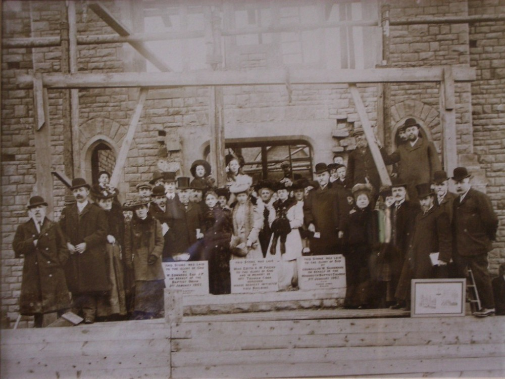 Monmouth Baptist Church building in mid construction in 1906 with members of the congregation in 1906.
