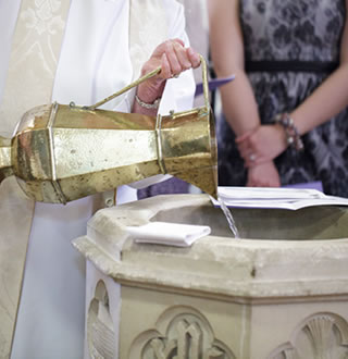 Priest fills font ready for baptism / christening