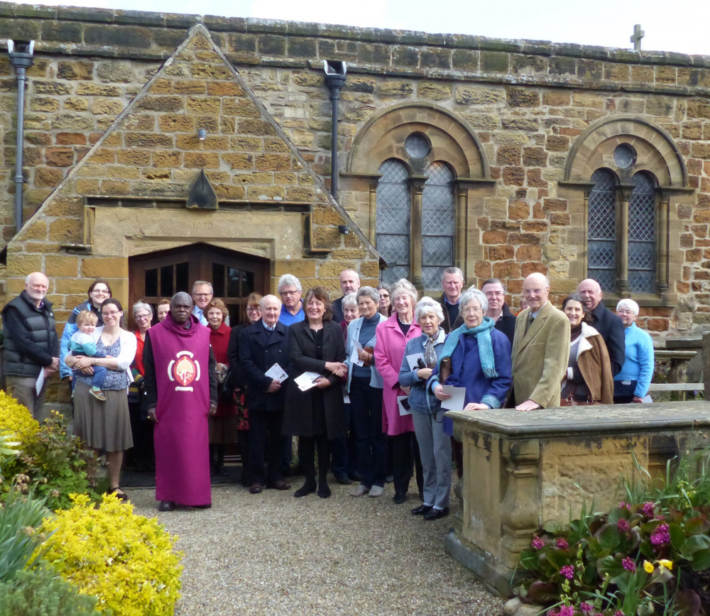 Group of people standing outside the porch of St Nicholas Church Husthwaite York