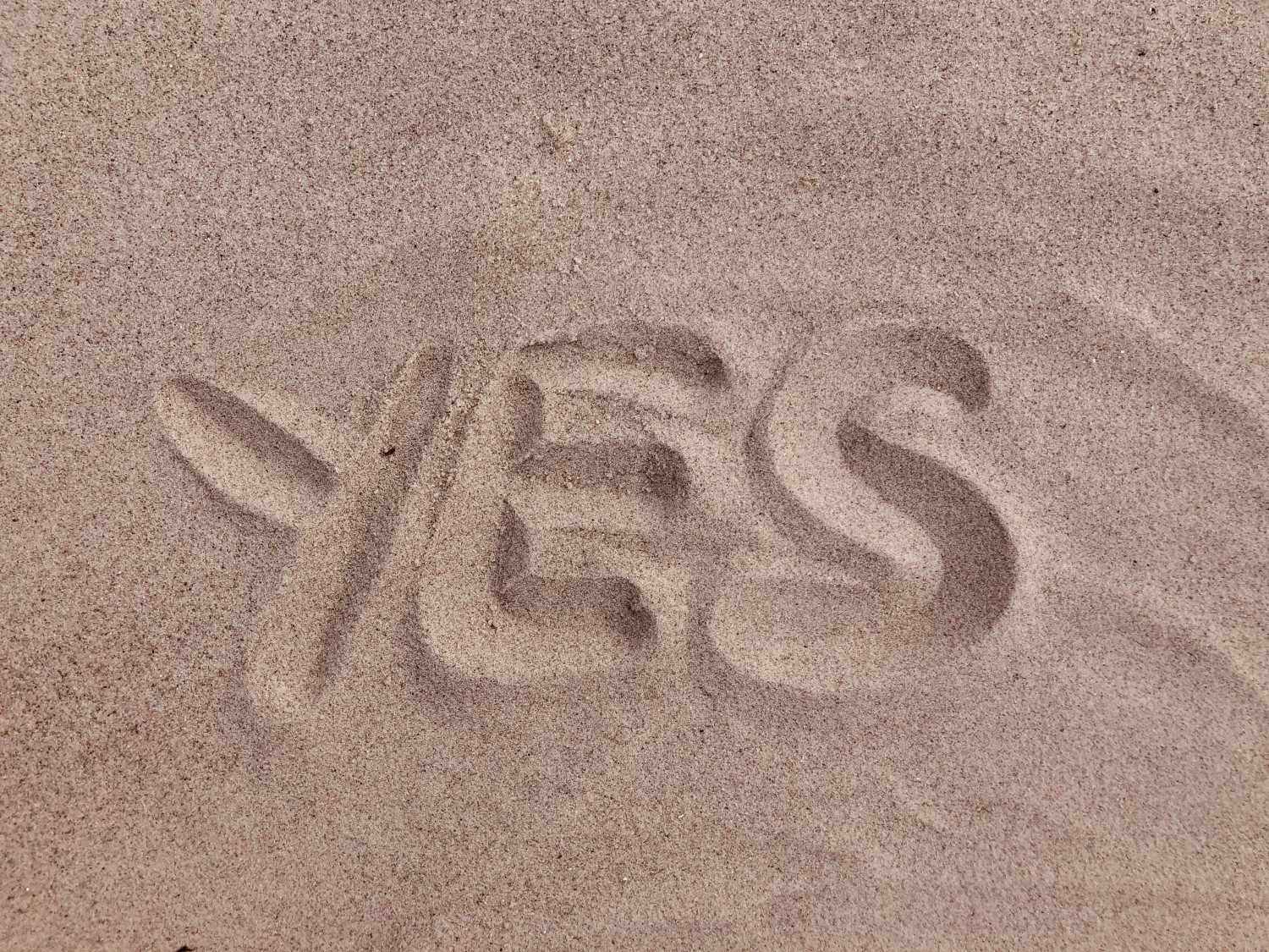 The word Yes written in sand
