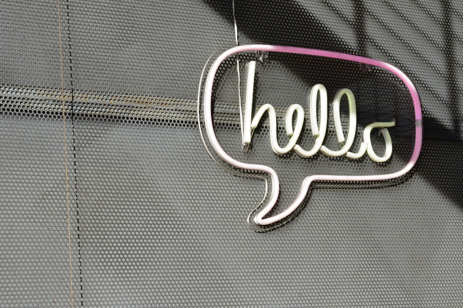 Neon sign with a speech bubble reading 'Hello'
