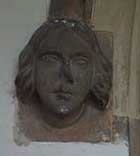 Carved head on left side of south door