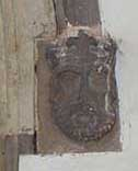 Carved head on right of south door