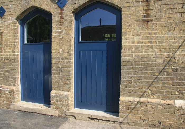 Rear kitchen windows in old door openings from courtyard