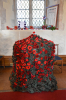 Knitted poppies over the font