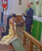 The couple kneel at the altar.