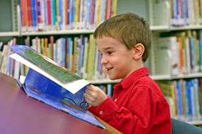 Boy reading a book in the library