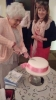 Beryl cuts the cake as Fiona looks on