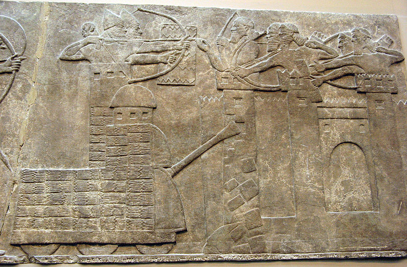 Assyrian attack on a town with archers and a wheeled battering ram ; Assyrian Relief, North-West Palace of Nimrud (British Museum)