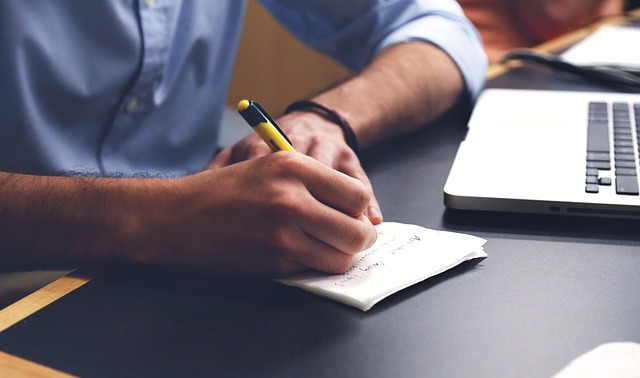image of person writing on a notepad