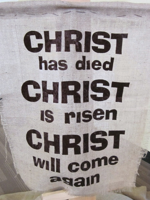 banner says 'Christ has died, Christ is risen, Christ will come again'